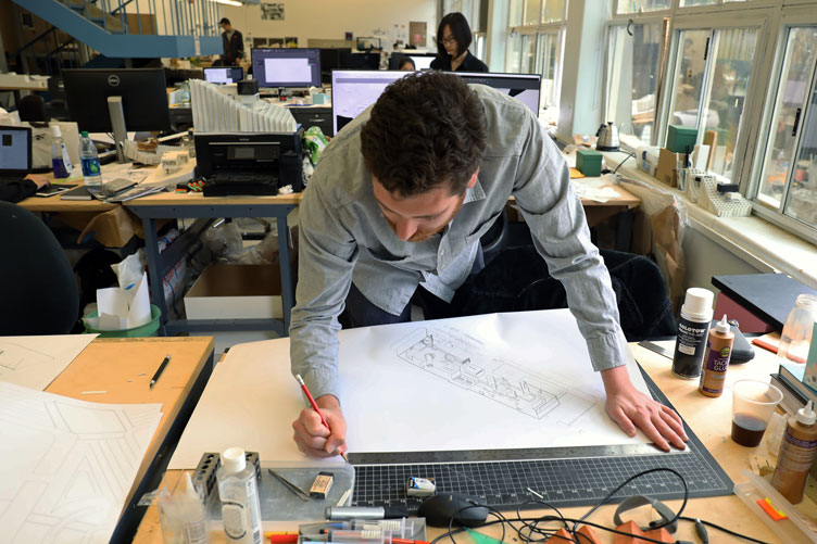 An architecture student marks measurements on a blueprint at a work desk.