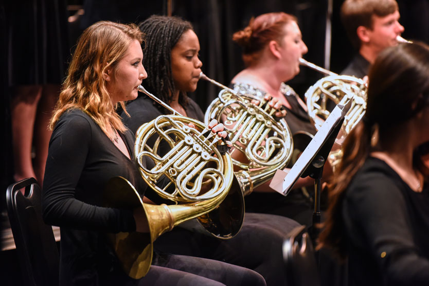 Music students play French horns in performance