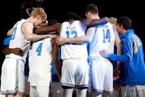 Men's basketball team players stand in a huddle.