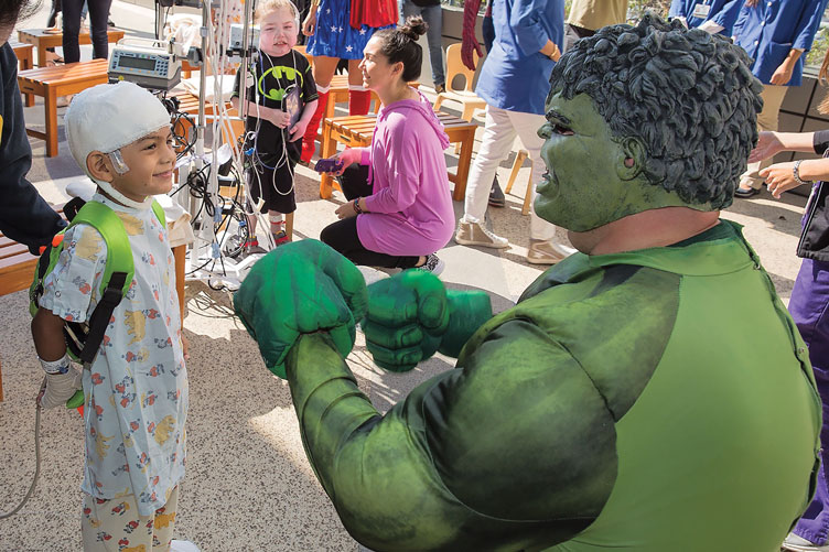 A Hulk character elicits a grin from a pediatric patient during UCLA Mattel's outdoor event.