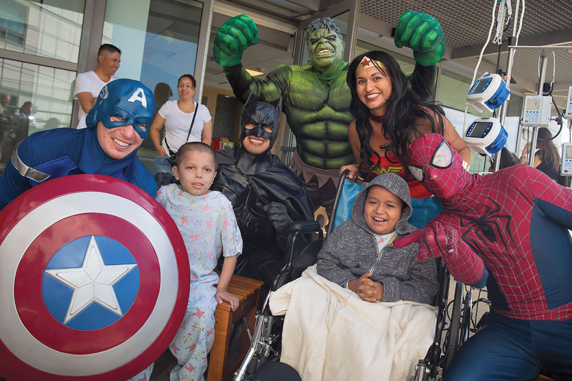 Captain America, Batman, the Incredible Hulk, Wonder Woman, and Spiderman characters pose with a child in a hospital gown sitting on a bench and a second child in a wheelchair.