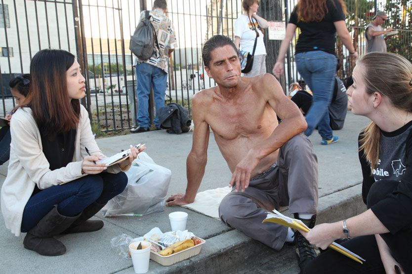 Two public health students provide food and interview a shirtless man sitting on a sidewalk