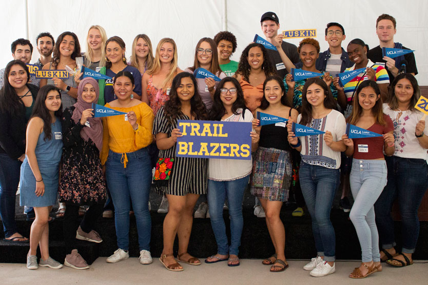 A group of students pose holding small Luskin and UCLA banners with a big sign that says TRAIL BLAZERS.