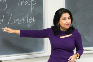 Professor Ananya Roy lectures using a chalkboard.