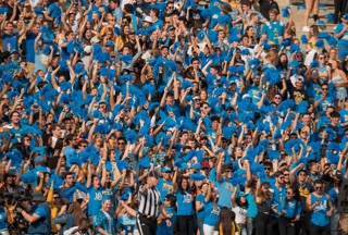 Crowd shot of UCLA fans in blue shirts cheering at a game