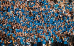 Crowd shot of UCLA fans in blue shirts cheering at a game.