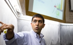 Professor Neil Garg gestures at a blackboard during a chemistry lecture.
