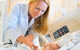 Female doctor with long blonde hair examines an infant in a hospital bed.