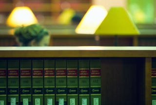 Shelf of legal reference books with library lamps glowing in the background