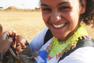 A woman holds a young child and smiles at the camera.