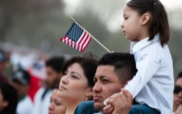 Young Latina girl holds a small U.S. flag and sits on her father's shoulders in a crowd.
