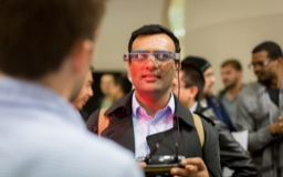 A man looks through augmented reality glasses; other people stand in the background.