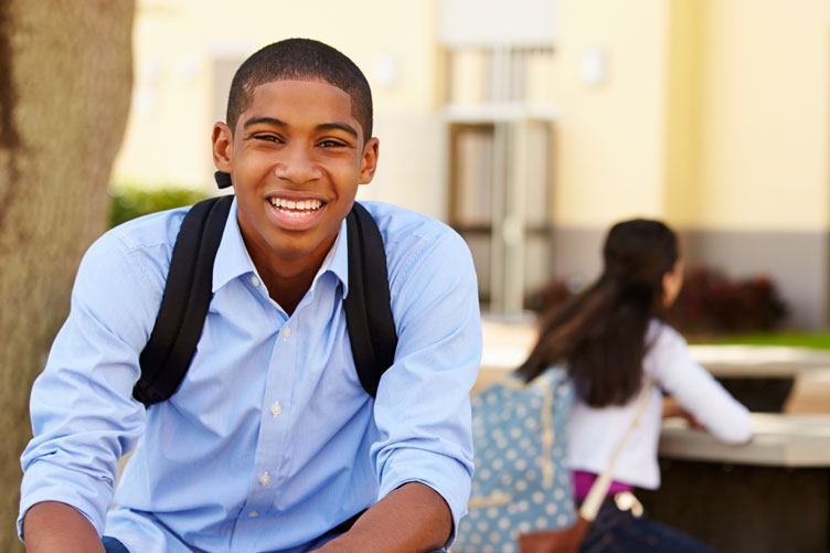 A young man wearing a backpack smiles at the camera as a young woman sits at a table in the campus background.