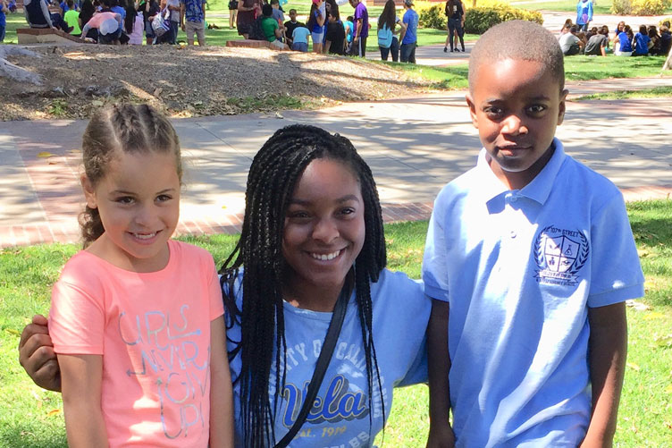 Amber Barnes poses with two young students on campus at UCLA.
