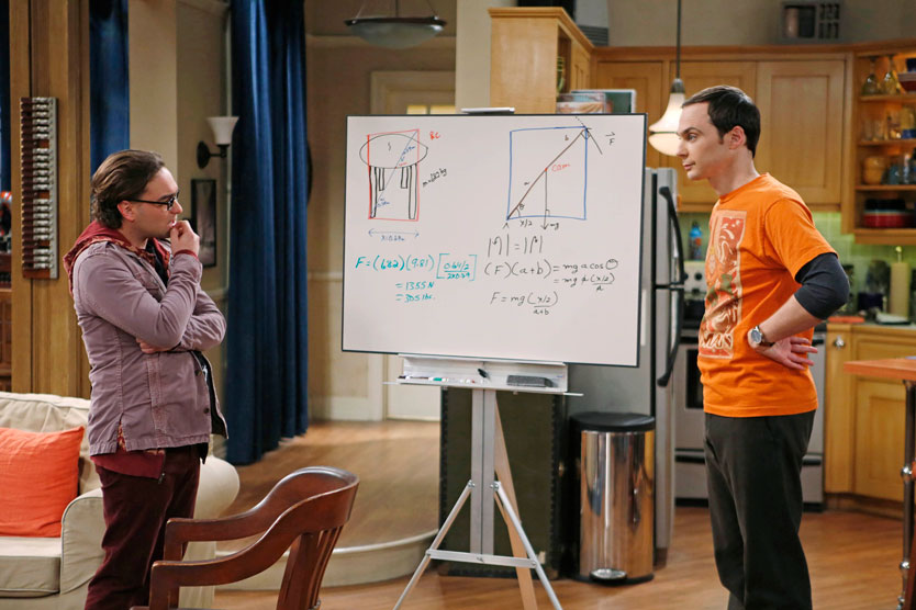 Two male cast members on The Big Bang Theory stand near a white board