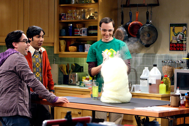 Three male cast members on The Big Bang Theory stand in the set kitchen while filming a scene.
