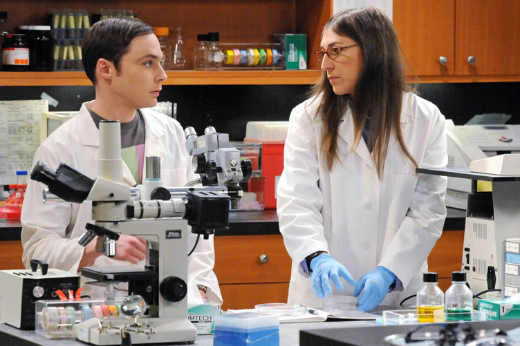 Two cast members--one male, one female--stand in a set for a laboratory