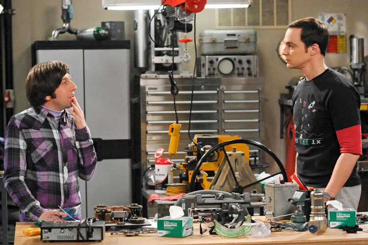 Two male cast members stand in a set designed to look like a workshop.