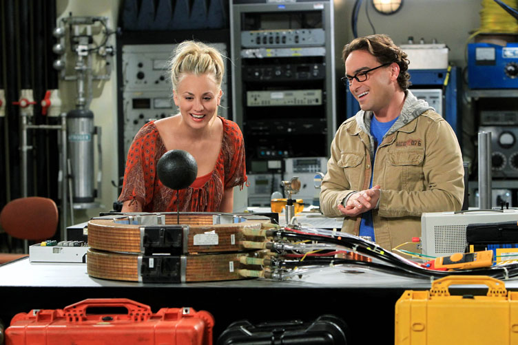 Two cast members--one female and one male--stand in a laboratory set.