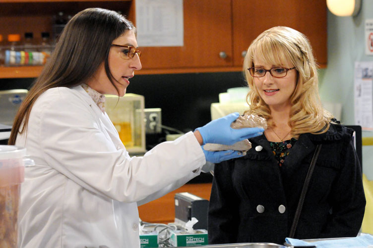 Two female cast members examine props during a scene.