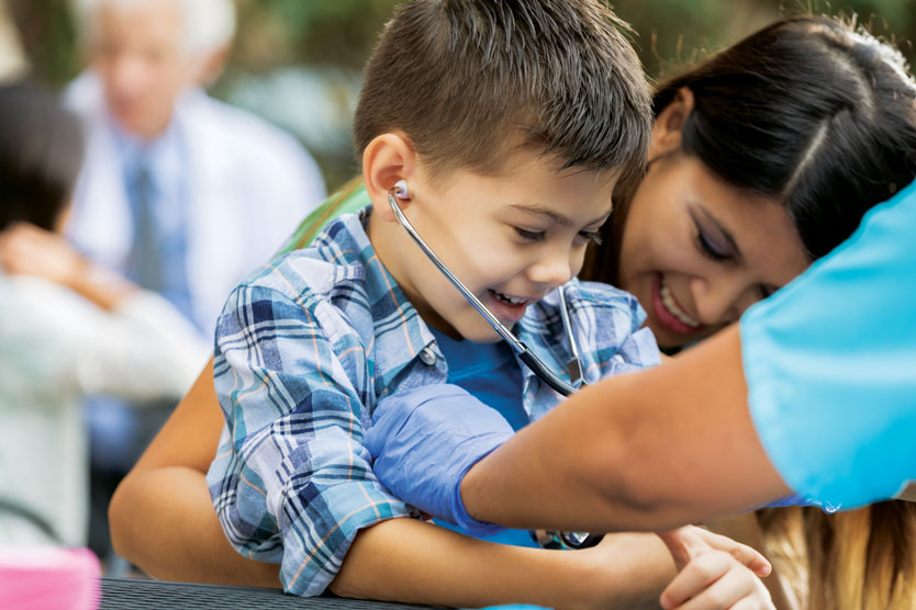 Young boy receives exam from community physician.