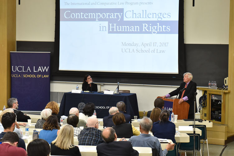 """Speaker at a podium presents to a lecture hall with """"Contemporary Challenges in Human Rights"""" on the screen behind him."""