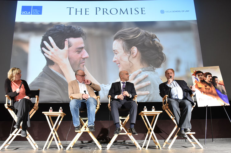 Four panelists sit on stage in front of a screenshot from The Promise film.