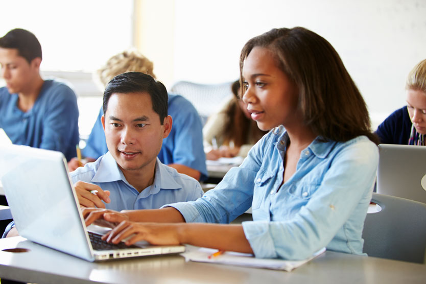 Teacher helping young student working on laptop.