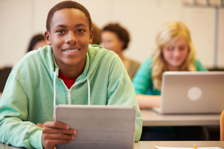 Young smiling student with laptop.