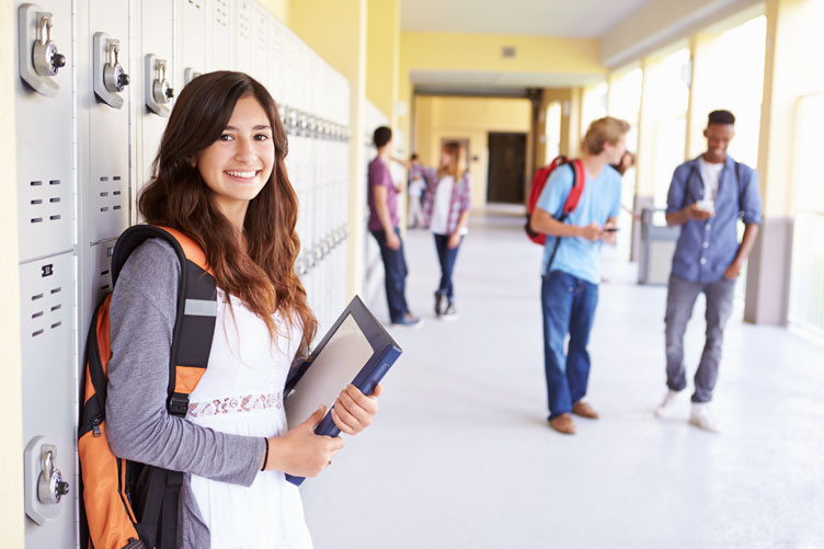 Young female student standing against lockers wearing backpack and with books in hand.