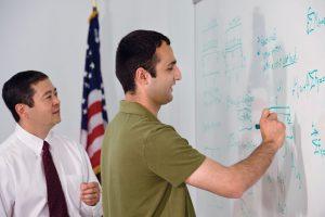 Man writing on whiteboard in classroom