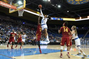 A UCLA women's basketball player shoots the ball over a USC defender during a game.