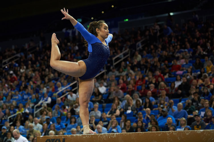 A UCLA gymnast performs on the balance beam during a competition.