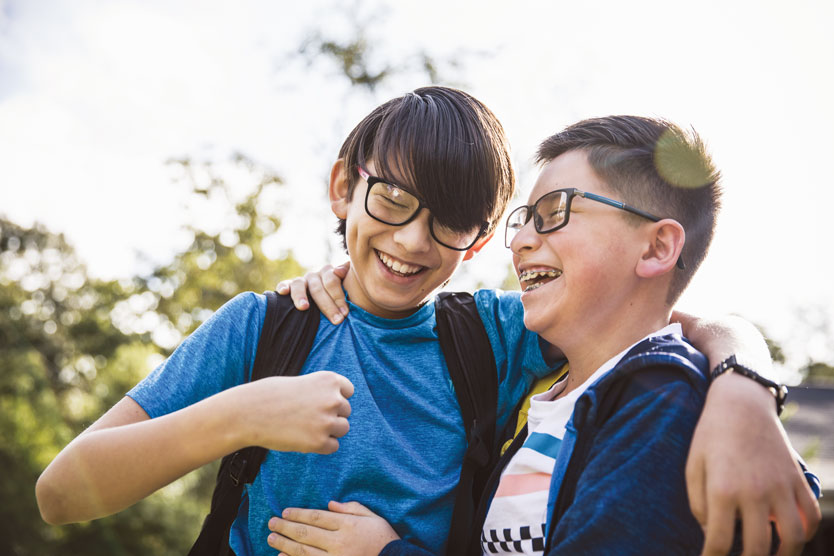 Two young boys share a joyful moment, laughing with their arms around each other.