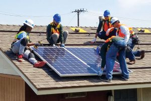 Five workers in hard hats and reflective gear install solar panels on the roof of a home.