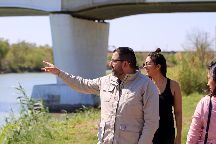 Professor speaks to students in the field while gesturing across a river.
