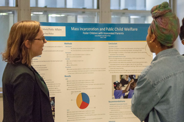 """Two women discuss a research poster entitled """"Mass Incarceration and Public Child Welfare: Foster Children with Incarcerated Parents."""""""