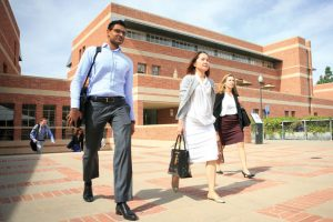 Three diverse graduate students in business dress stride confidently across UCLA's campus.