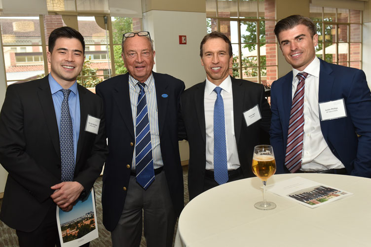 Bill Cockrum poses for a photo with two students and a fellow advisor at an event.
