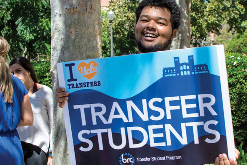 Smiling student holds a sign for transfer students in the BRC Transfer Student Program.