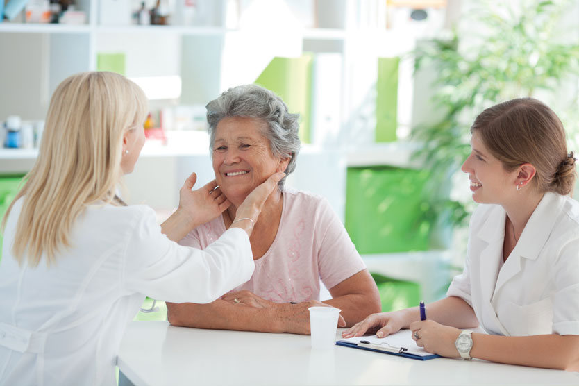 Older woman getting throat examined by physician.