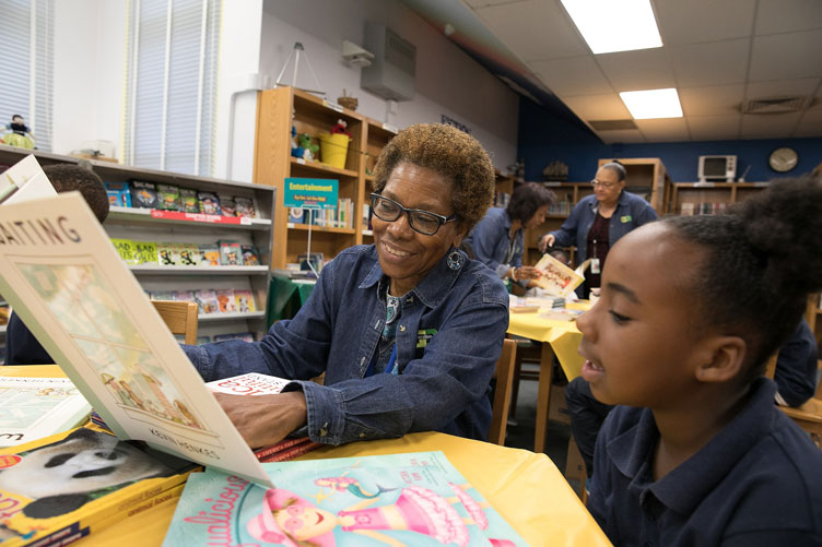 Older Generation X-change volunteer reads to a young student as additional volunteers work in the background.
