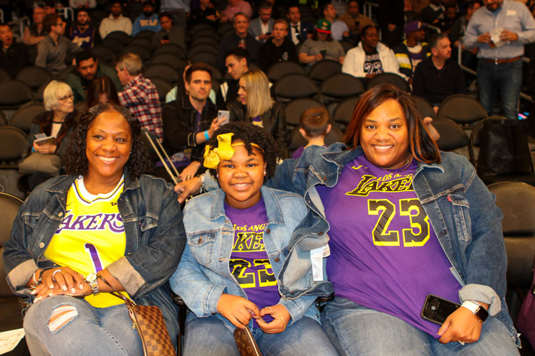Two women and a young girl in Lakers shirts in their seats in the arena