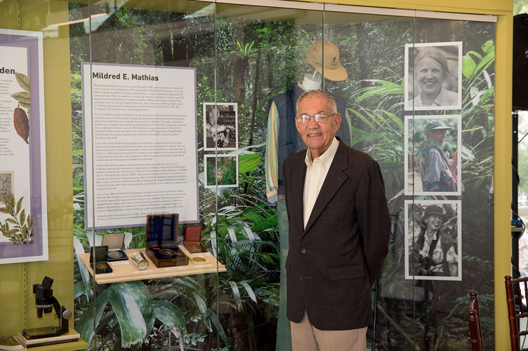 Donor Morton La Kretz stands in front of a display featuring information, photos, and memorabilia related to Mildred E. Mathias.