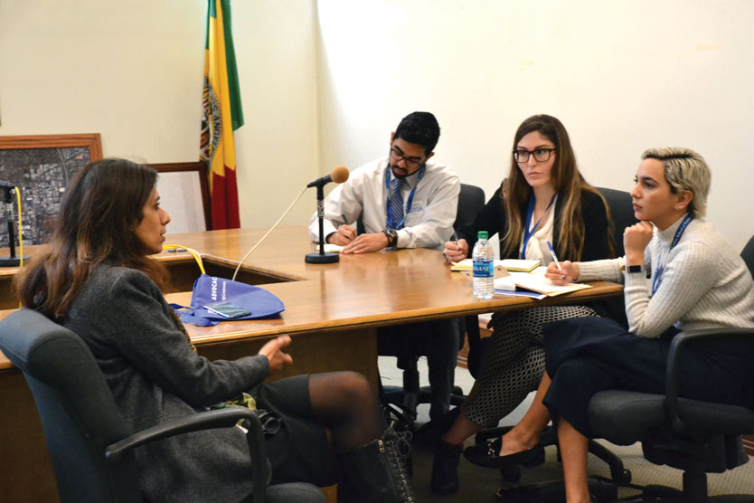 Luskin scholarship students sit at a table conversing with a woman