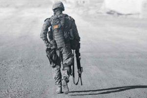 Soldier in gear in desert walking away from camera