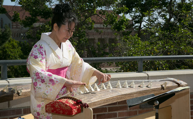 Woman in kimono plays traditional Japanese instrument