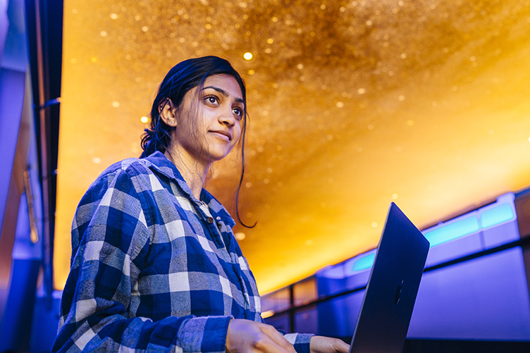 Young woman with dark hair pulled back, wearing a blue and white checked shirt, uses a laptop; the ceiling above her looks like a starry golden sky