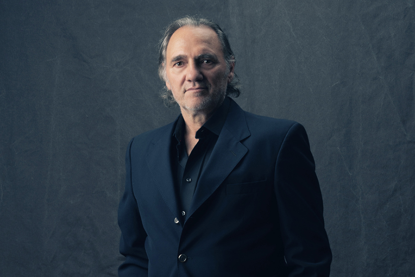 Distinguished Professor Carlos Alberto Torres, a Latino man with grey hair, wears a black collared shirt and suit jacket and stands in front of a dark background