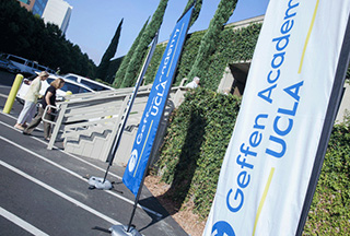 Three free-standing flags showing the Geffen Academy at UCLA logo stand outside the entrance to the ivy covered building